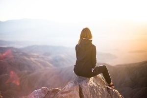 how to change your life for the better cover image for blog post of a girl sitting on a rock on a mountain looking out